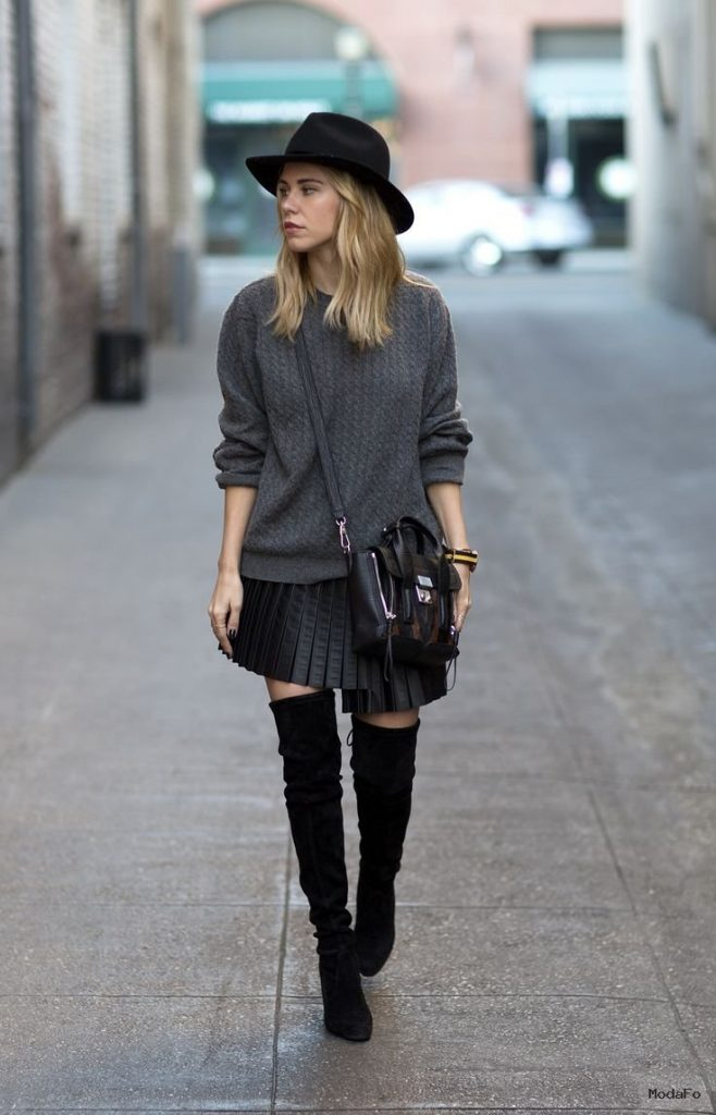 Black hat, grey sweater, leather pleated skirt, overknee boots …
